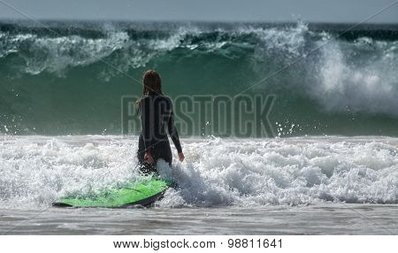 Lady surfer walking with surf board towards the ocean