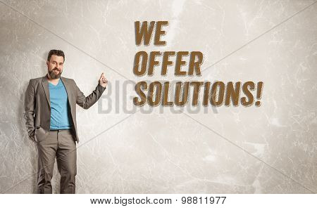 Businessman Pointing Up Towards Text, We Offer Solutions