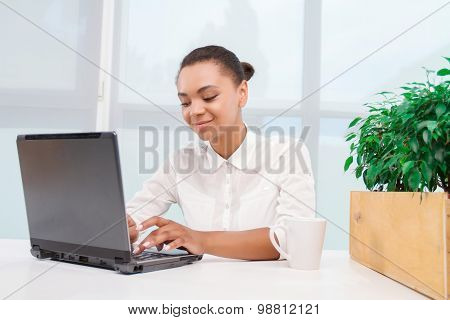 Pretty mulatto girl working on computer