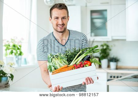Young Man With Vegetable Box In Kitchen