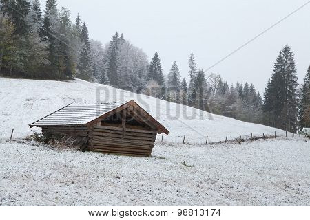 Wooden Hut On Winter Alpine Meadow