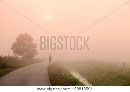 Biker On The Road At Misty Sunrise