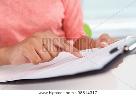 Close-up of woman holding folder with papers