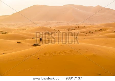 Local man crossing sand dunes in Merzouga, Morocco, at sunset