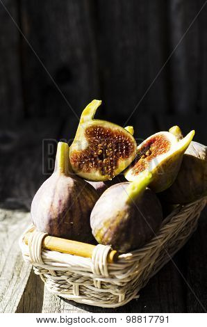 Ripe figs in the little backet  on the old wooden table