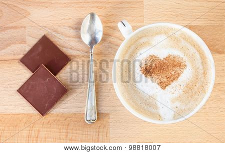 The cup of cappuccino with cinnamon heart