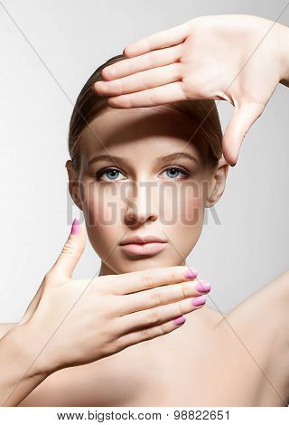 Closeup portrait of woman makes focus composition frame with hands