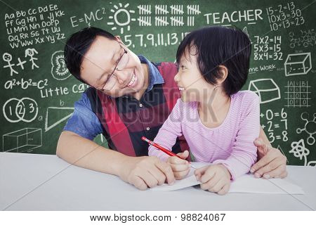 Male Teacher Teach Little Girl In Class