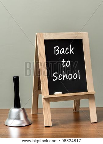Silver handbell and blackboard with Back to School phrase placed on brown desktop over green wall