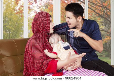 Man Scolding His Wife While Holding Baby