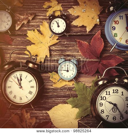 Autumn Leafs And Alarm Clock On Wooden Table.