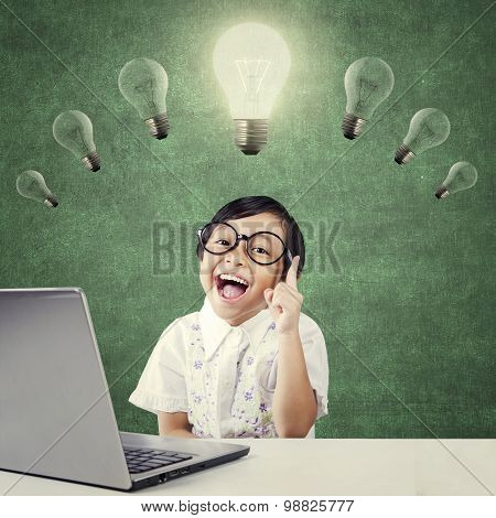 Smart Kid Sitting Under Lamp With Laptop
