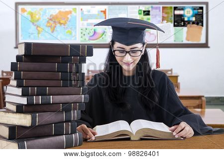 Student Studying In The Class While Wearing Mortarboard