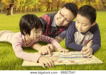 Two Kids And Dad Reading A Book While Lying At Park