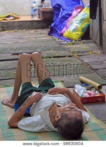 homeless skinny man is lying on the pavement in Hanoi