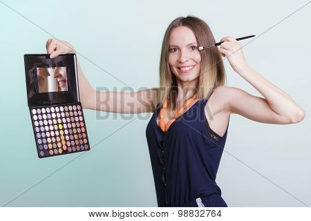 Woman Applying Eyeshadow With Makeup Palette.