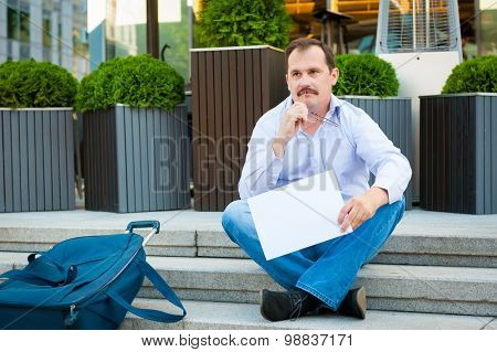 Sad businessman sitting on the steps with a empty poster