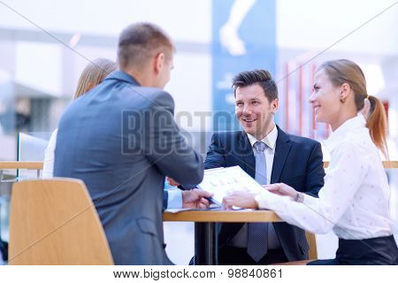 Group of happy young business people in a meeting at office .