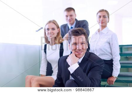 Business people sitting on the ladder in office .