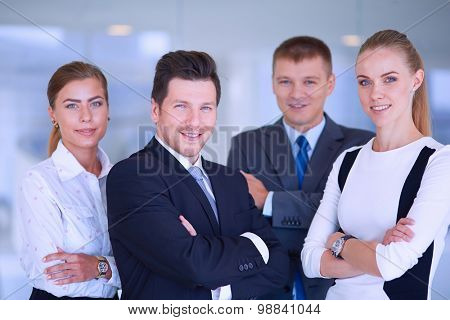 Smiling successful business team standing in office .