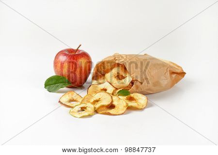 fresh red apples and dried apple rings spilt out of paper bag