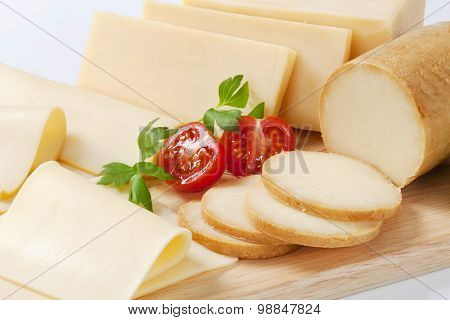 variety of sliced cheeses on wooden cutting board