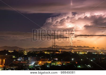 Sky With Lightning Striking Hills Behind Small Town