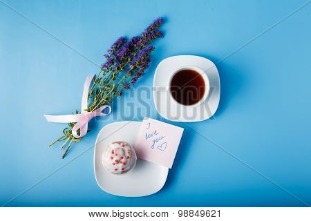 Colorful Muffin On Saucer With Flowers. Top View