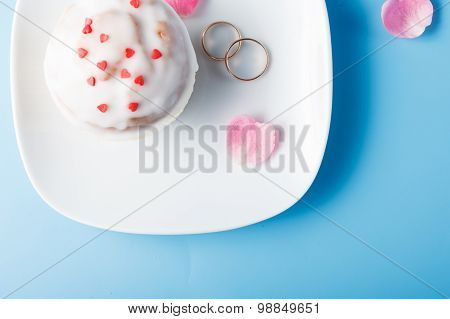Colorful Muffin On Saucer With Wedding Rings. Top View