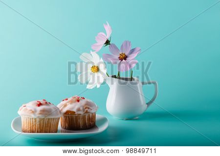 Colorful Muffin On Saucer With Flower. Aqua Color Background