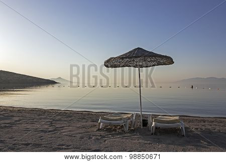 Two Sunloungers On Early Morning Beach