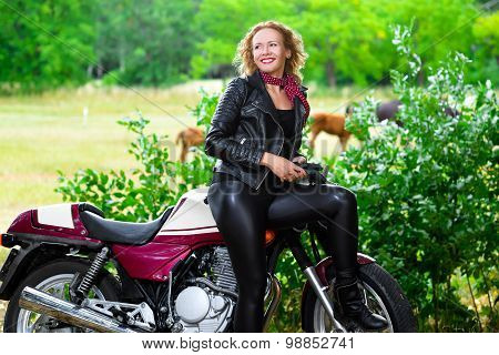 Biker girl in leather jacket on a motorcycle
