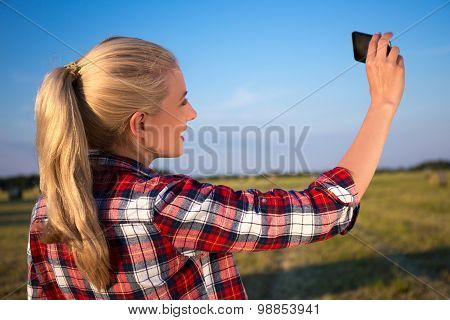 Back View Of Blonde Woman Making Selfie Photo On Smartphone In Meadow