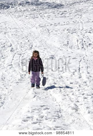 Little Girl Plays With Sledging In Winter On The White Snow