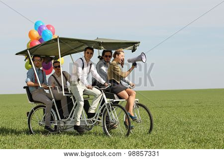 baloons woman leading 4 guys on a quad bike on a green field sunny day
