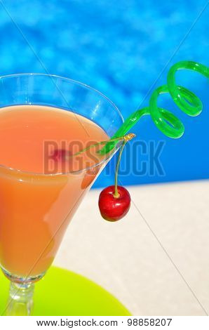 Glass Of Juice And A Cherry On A Green Plate