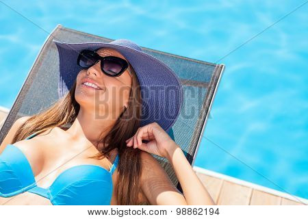 Cheerful young woman is resting on the sun