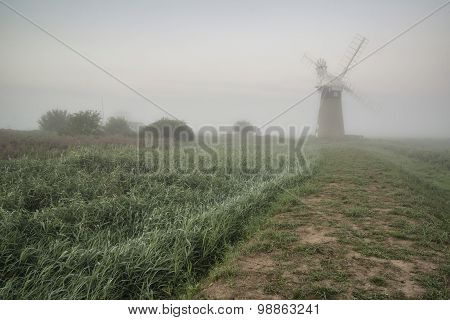 Old Windmill In Foggy Countryside Landscape In England
