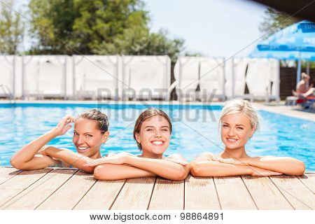 Cheerful young girls are swimming in blue water