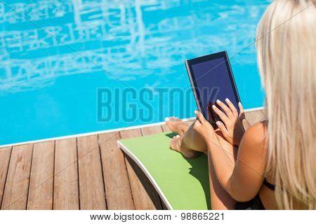 Pretty young girl is getting suntan near water