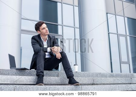 Attractive young businessman is resting after work