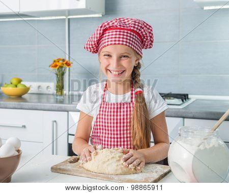 cute little girl kneading a dough on a kitchen