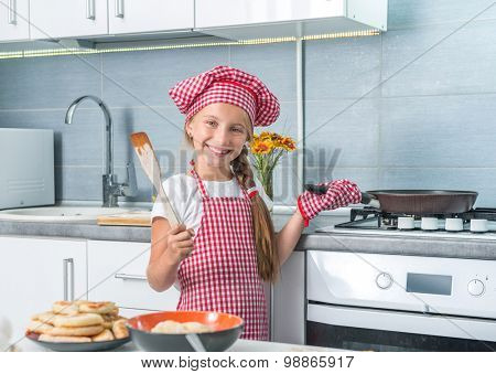 smiling little girl roasting patties on a pan and a plate of done patties