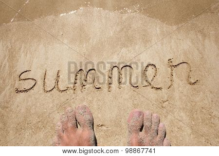 Summer hand written in sand on a beach on an exotic island background with feet