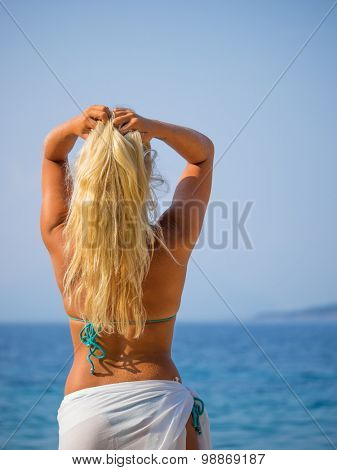 Youmg woman with sarong woman standing on the beach