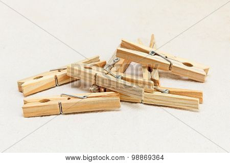 Heap Of Wooden Clothespins On White Fabric Background.