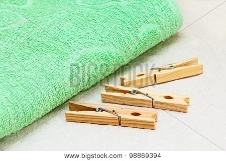 Green Towel And Wooden Clothespins On White Fabric.