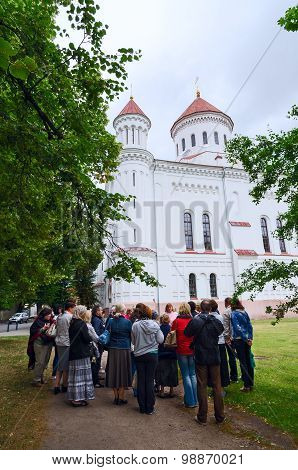 Tourists Listen To Story Of Guide Before Visiting Pretchistensky Cathedral In Vilnius