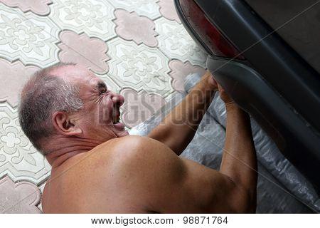 Senior Mechanic Working Under A Car