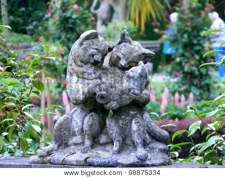 Sculptural group - the cat family of gray stone in the garden